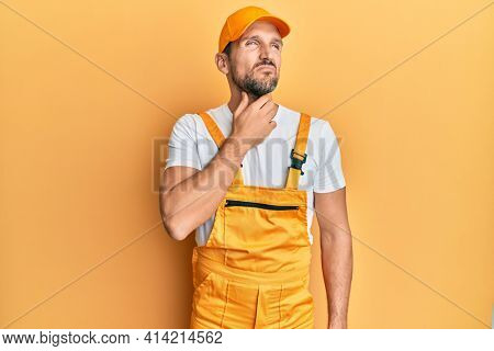 Young handsome man wearing handyman uniform over yellow background touching painful neck, sore throat for flu, clod and infection