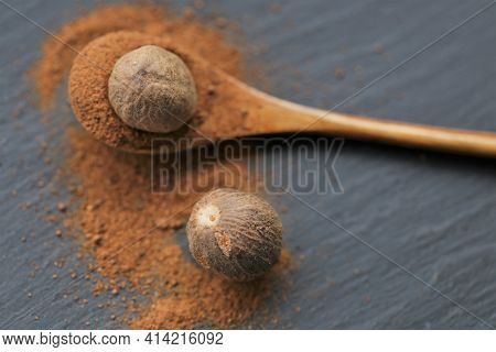 Nutmeg .whole And Ground Nutmeg In A Wooden Spoon On A Schiffer Background. And Herbs Concept.food I