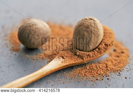 Nutmeg .whole And Ground Nutmeg In A Wooden Spoon Close-up On A Schiffer Background. And Herbs Conce