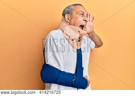 Handsome mature senior man wearing cervical collar and arm on sling shouting and screaming loud to side with hand on mouth. communication concept.