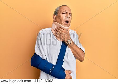 Handsome mature senior man wearing cervical collar and arm on sling touching painful neck, sore throat for flu, clod and infection
