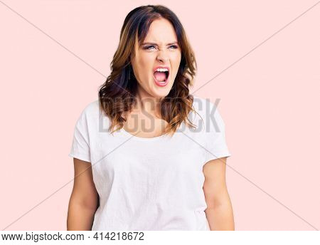 Young beautiful caucasian woman wearing casual white tshirt angry and mad screaming frustrated and furious, shouting with anger. rage and aggressive concept.