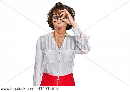 Young hispanic woman wearing business style and glasses doing ok gesture shocked with surprised face, eye looking through fingers. unbelieving expression.