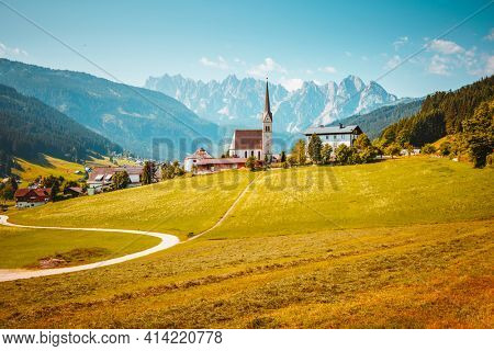 Picturesque touristic alpine village with Pfarrkirche Catholic church on a sunny day. Location place Gosau village, Upper Austria, Europe. Summer trip. Photo wallpaper. Discover the beauty of world.
