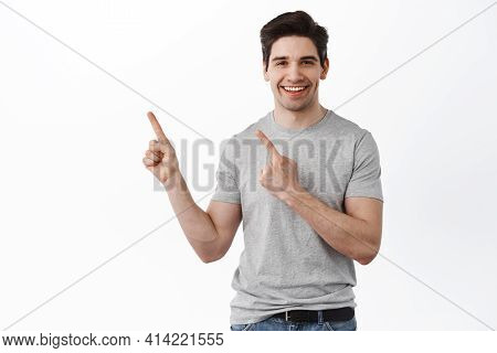 Handsome Caucasian Man Smiling, Pointing Upper Left Corner, Showing Promo Text Aside On Copyspace, S