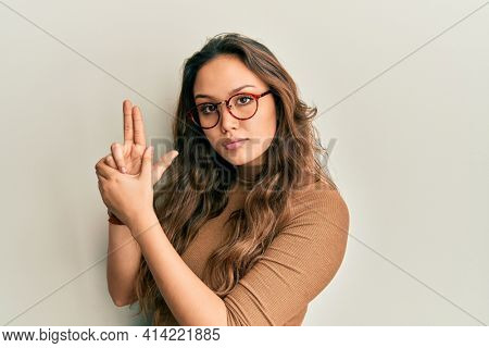 Young hispanic girl wearing casual clothes and glasses holding symbolic gun with hand gesture, playing killing shooting weapons, angry face