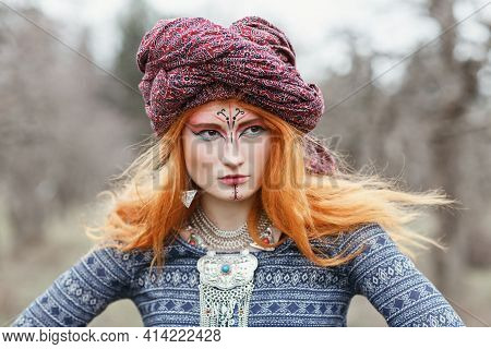 Portrait Of Extravagant Redhead Young Woman Wearing Ethnic Jewelery, Clothes And Turban With Unusual