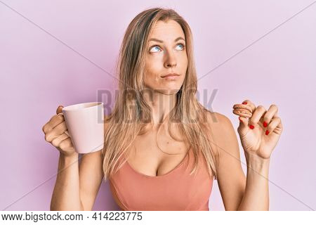Beautiful caucasian woman drinking coffee and eating french pastry macaron smiling looking to the side and staring away thinking.