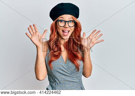 Young redhead woman wearing fashion french look with beret celebrating crazy and amazed for success with arms raised and open eyes screaming excited. winner concept
