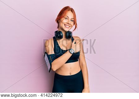 Young beautiful redhead woman wearing gym clothes and using headphones cheerful with a smile of face pointing with hand and finger up to the side with happy and natural expression on face