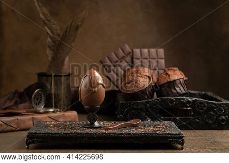 Brown Chocolate Egg With Flowing Liquid Chocolate On A Stand On A Brown Background. Muffins And Choc
