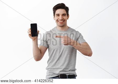 Portrait Of Smiling Adult Man Pointing And Showing Empty Smartphone Screen, Showing Blank Display Ph