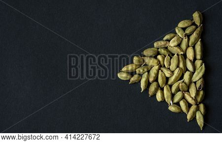 Close Up Photo Of Cardamom Pods Pile Formed As Play Sign Icon On The Matt Black Background. Cardamom