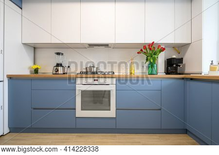 Front view of well designed blue-teal and white modern kitchen interior