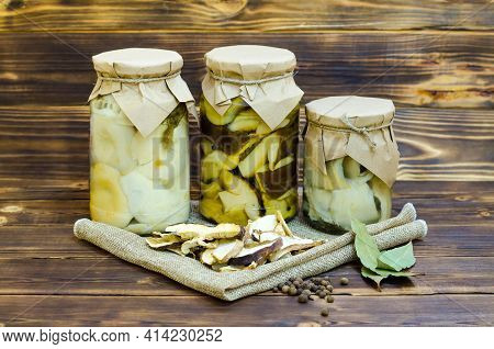 Pickled Mushrooms In Glass Jars On A Wooden Background. Mushrooms With Herbs And . Homemade Food. Pi