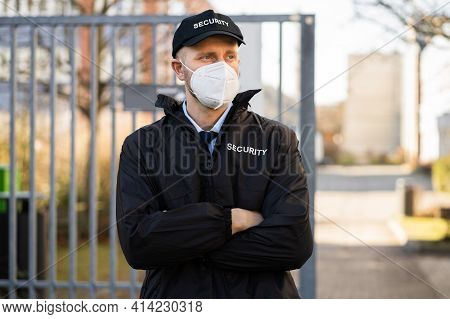 Security Officer In Covid Face Mask Outside Building