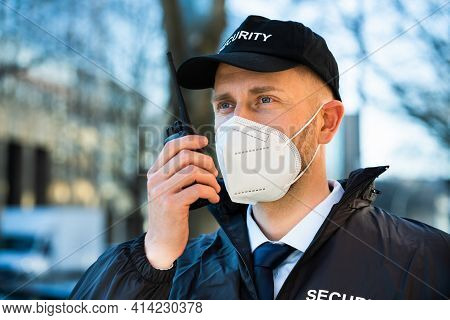 Security Officer In Ffp2 Covid Mask Using Walkie Talkie