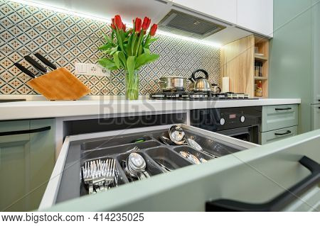 Drawers with silverware and other kitchen utensils pulled out with content in cabinet at luxury teal and white modern kitchen furniture