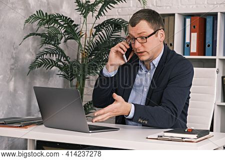 Portrait Of An Indignant Man In A Classic Suit And Glasses, Pointing At A Laptop Monitor, Talking On