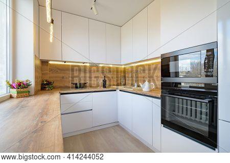 Well designed white and wooden beige modern kitchen interior