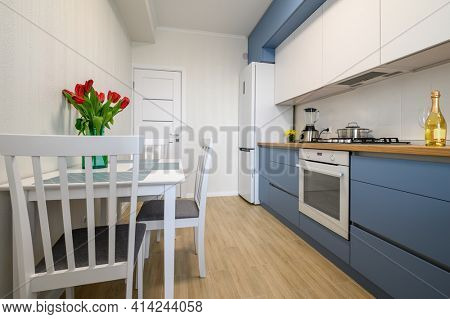 Details of cozy well designed teal-blue and white modern kitchen interior