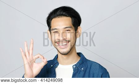 Close Up Of Young Asian Man Showing Ok Hand Sign And Smiling While Standing Over Isolated Grey Backg