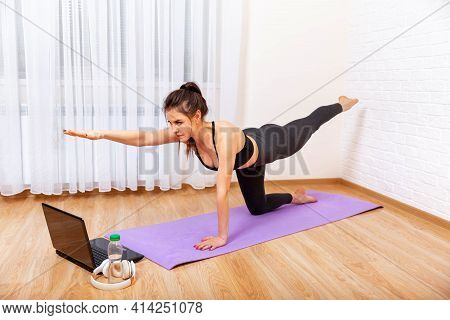Young Sporty Woman Practicing Yoga. Achieving Sound Of Mind Through Yoga. Woman Exercising At Home I