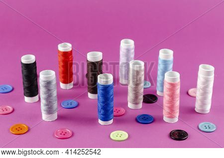 Multicolored Thread Spools And Buttons On Purple Background. A Set Of Thread Stands Vertically. Ten