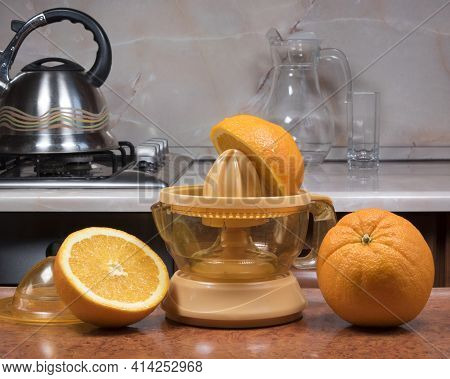 Manual Juice Extractor. Juicing Oranges. Electric Press Juicer With Cut Orange On Kitchen Table At H