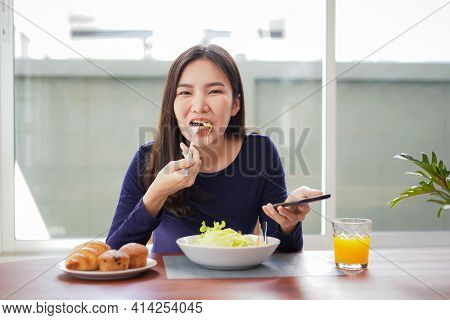 Young Asian Woman Eating Healthy Salad With Fresh Vegetable On Wellness Lifestyle And Looking On Sma