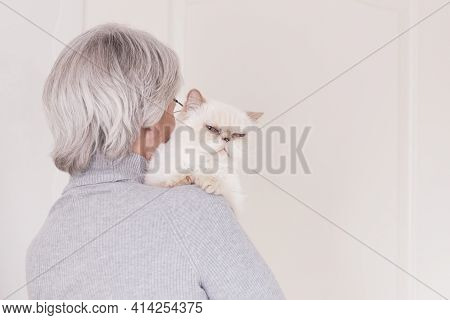 A Gray-haired Older Woman In A Gray Turtleneck Has A Cute Beige Cat On Her Shoulder. The View From T