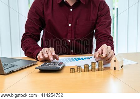 Asian Business Man Putting Coin Increase On Coins Stacking With House Model During Using Calculator