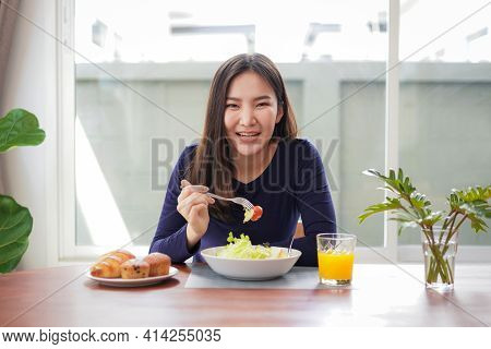 Young Asian Woman Eating Healthy Salad With Fresh Vegetable And Dip Tomato With A Fork While Looking