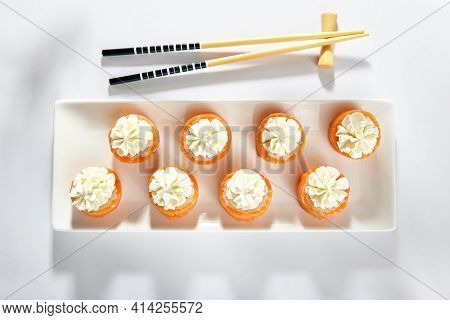 Philadelphia Sushi Roll made with Smoked Salmon. Maki sushi topped with cream cheese. White plate with wooden chopstick on white table. Top view