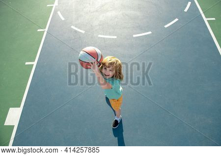 Cute Smiling Boy Plays Basketball, Outdoor On Playground. Child Shooting Basketball Ball And Playing
