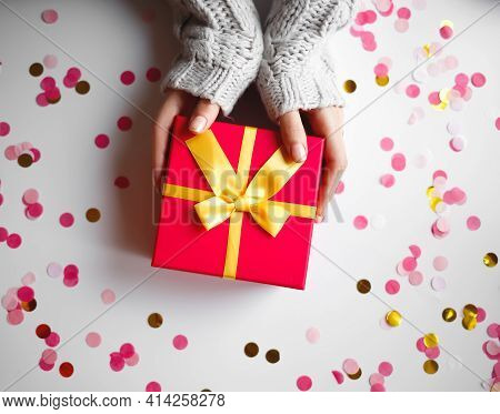 Female Hands With Beautiful Manicure Hold A Gift Box
