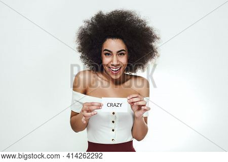 Totally Crazy. Playful Young African Woman Smiling And Holding A Piece Of Paper Which Is Saying Craz