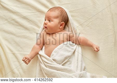 Newborn Baby After Shower Wrapped In Towel Lying On Bed On White Blanket, Infant Looking Away, Charm