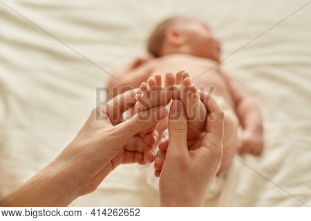 Faceless Person Making Baby Massage For Infant Lying On Bed, Mommy Massaging New Born Baby With Love
