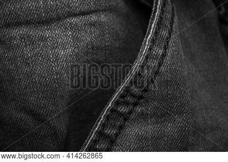 Black Denim With Stitching Details. Background On The Theme Of Denim Clothing.