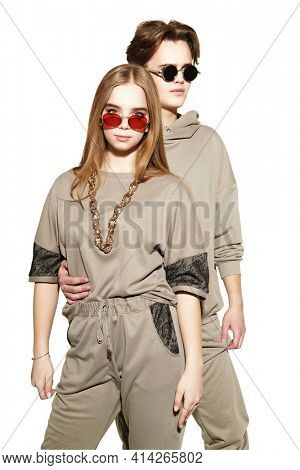 Two modern teenagers a boy and a girl pose together in fashionable sportswear at studio. Sport style. White background.