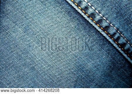 Background On The Theme Of Denim Clothing. Denim Fabric With Elements Of Seams.