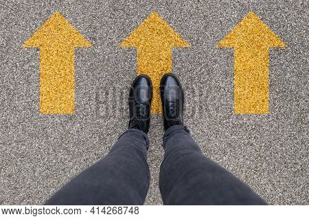 Black Shoes Standing On The Asphalt Concrete Floor With Three Yellow Direction Arrows Symbol. Moving