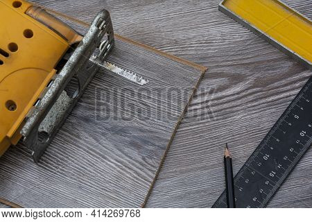 Construction Square, Jigsaw And Pencil On The Laminate. Equipment For Installing Laminate Flooring.