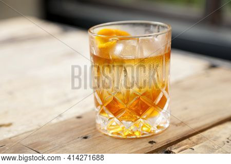 Old Fashioned Cocktail With Whiskey On A Wood Table.