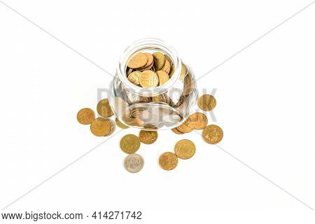Metal Coins In A Glass Jar Isolated On A White Background. Keeping Personal Savings. Financial Crisi