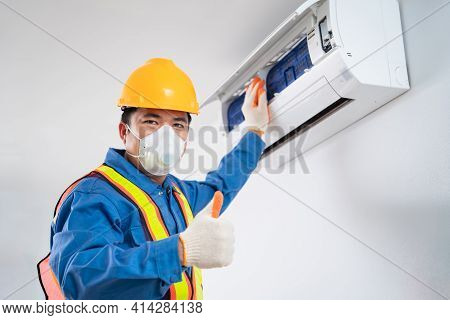 Happy Asian Male Wear A Safety Mask To Prevent Dust Technician Cleaning Air Conditioner Indoors, Air