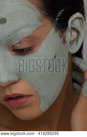 Skin Care Mask. Closeup Portrait Half Face Of Attractive Young Woman With Grey Clay Facial Mask On H