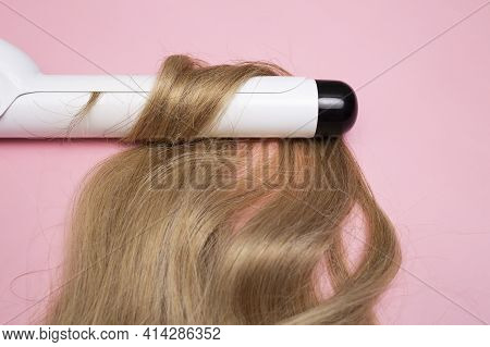 Curling Blonde Hair On A Large Diameter Curling Iron On A Pink Background. Curl Care, Hair Styling.