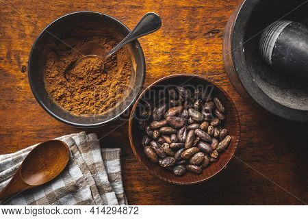 Roasted cocoa beans and cocoa powder in bowl on wooden table. Top view.
